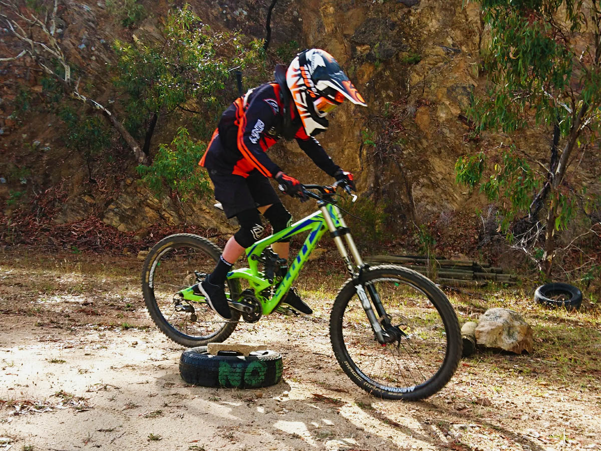 A rider controls his bike over a small obstacle