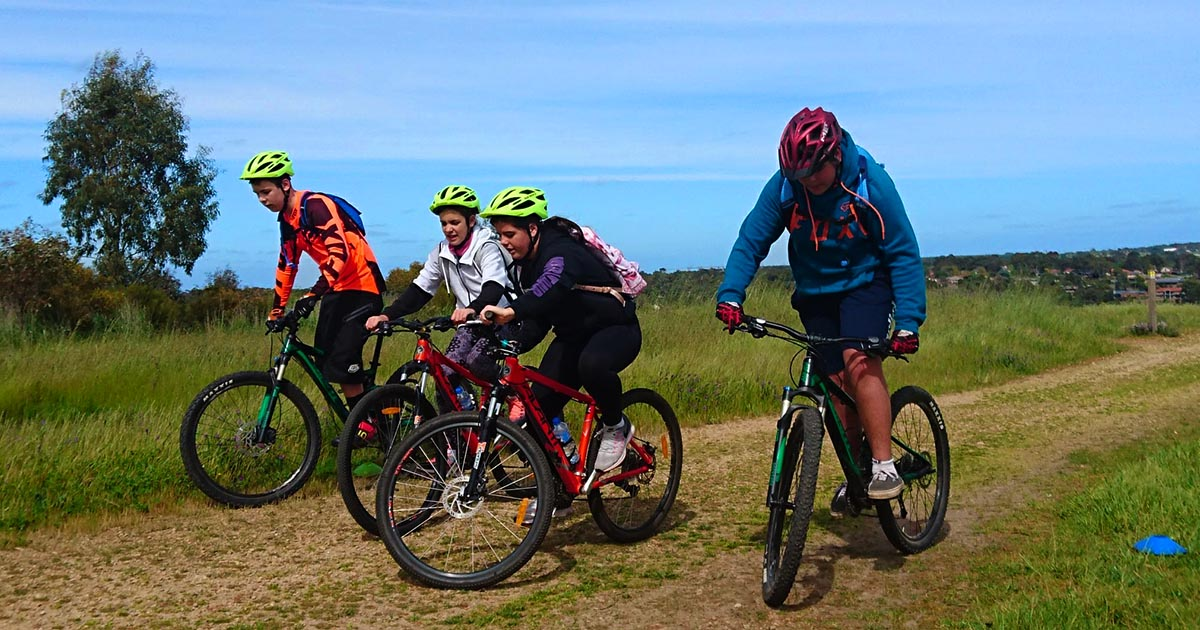 A group of young mountain bikers in a slow race