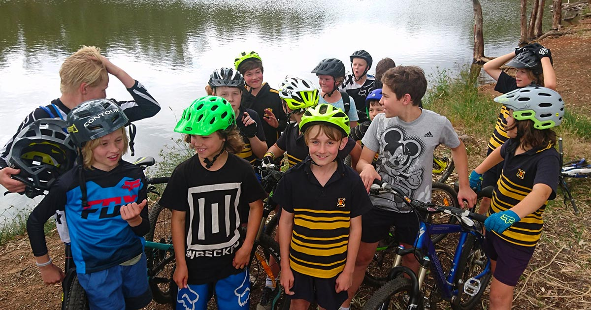 A group of young mountain bikers in front of a lake