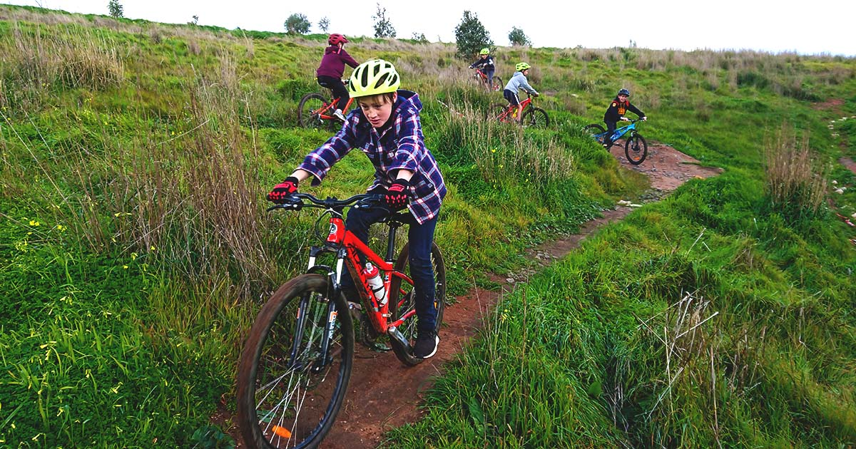 A group of young riders on a mountain bike trail
