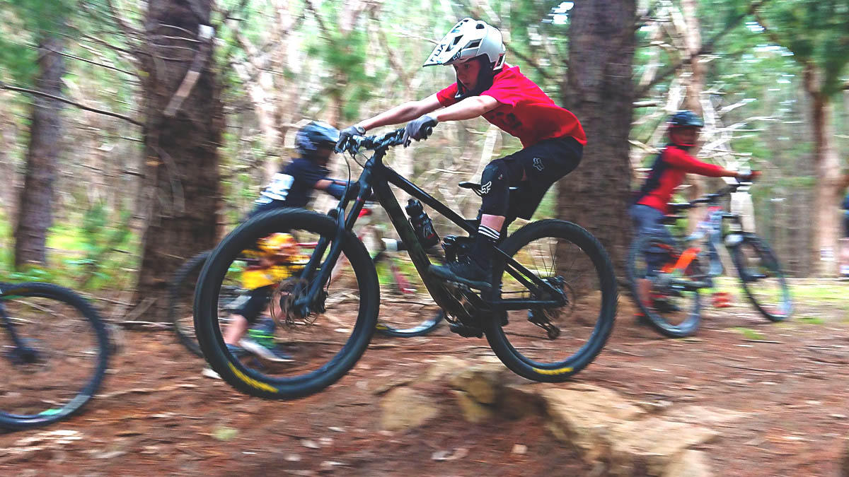A junior gravity enduro rider practising drop off technique