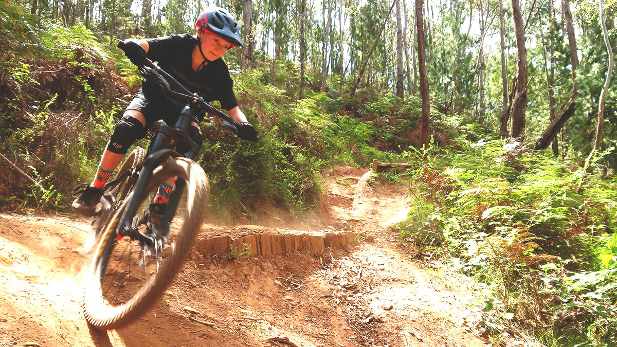 A junior downhill rider enters a steep section of trail