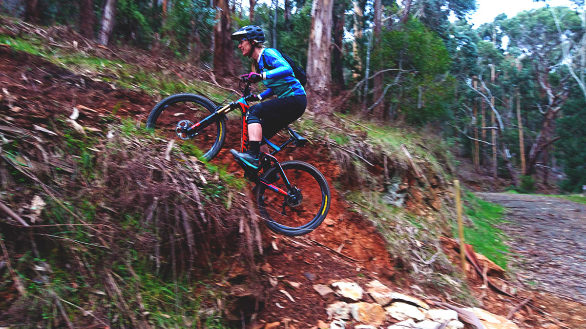 A woman powers her bike up a steep section of trail