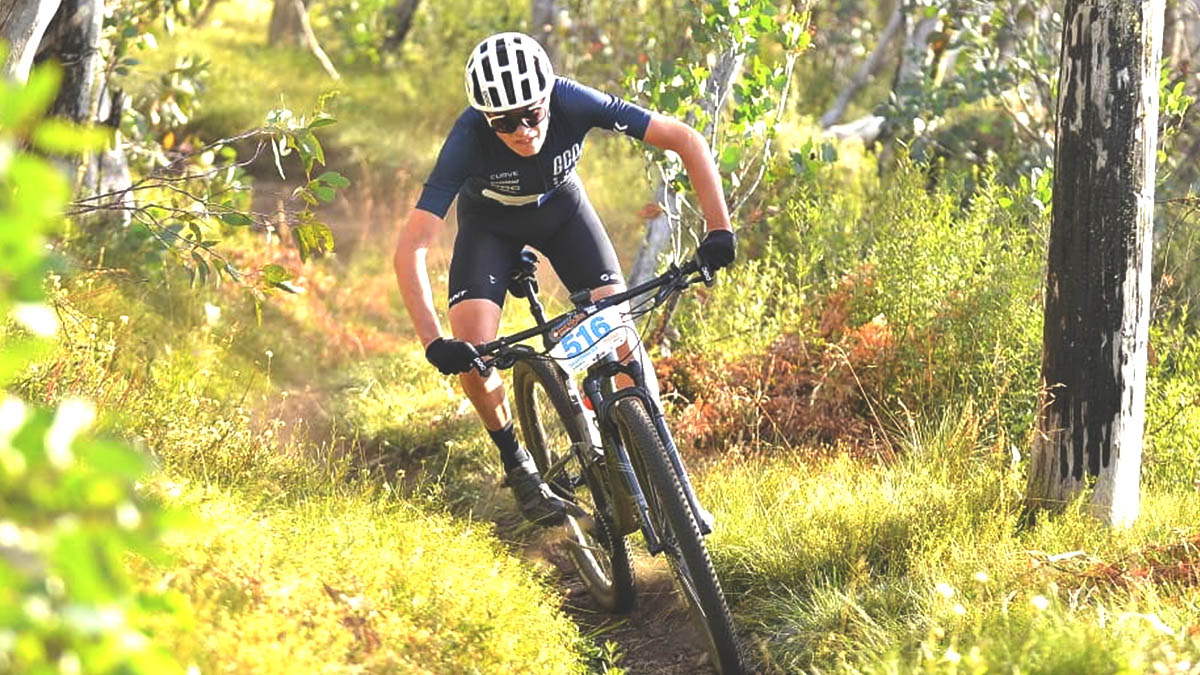 A cross country mountain biker riding in the attack position