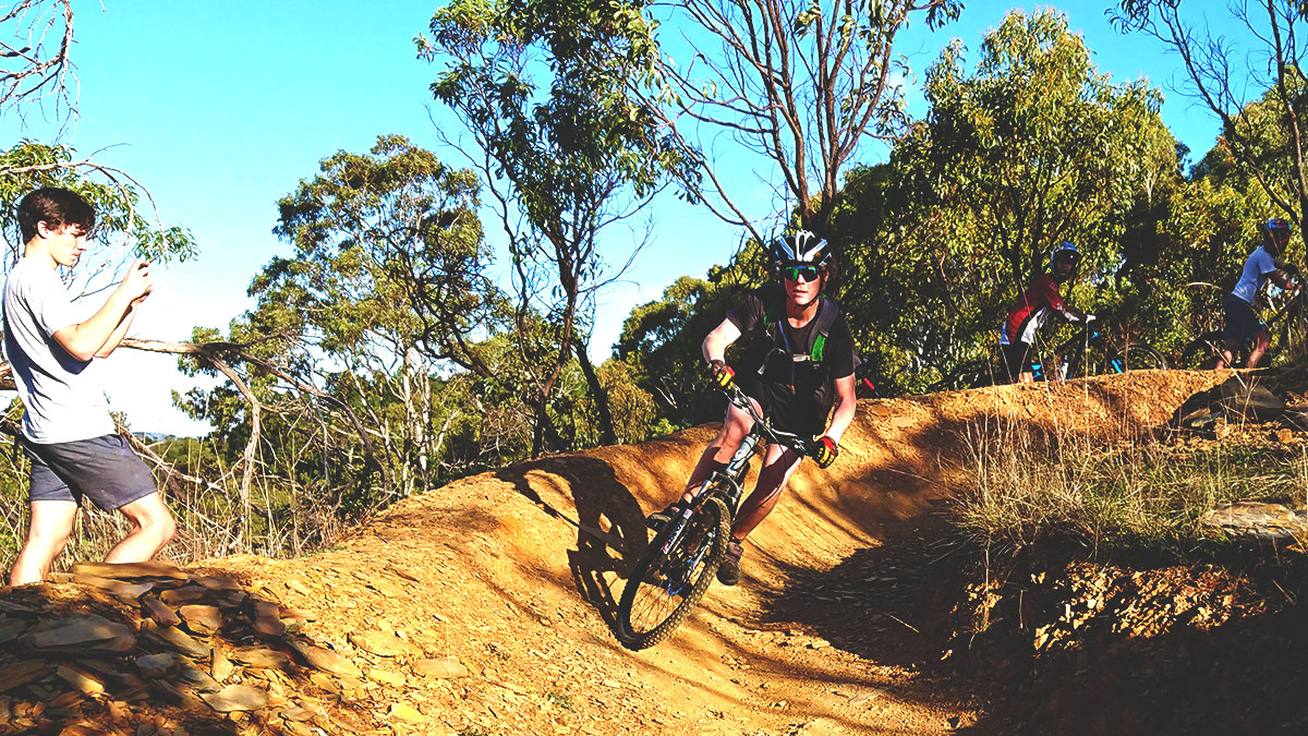 A group of students practise their cornering skills on a school mountain bike camp
