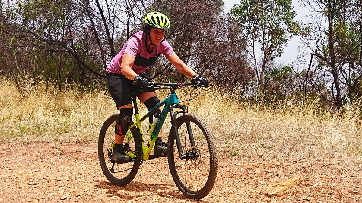 A women practises body position on her mountain bike